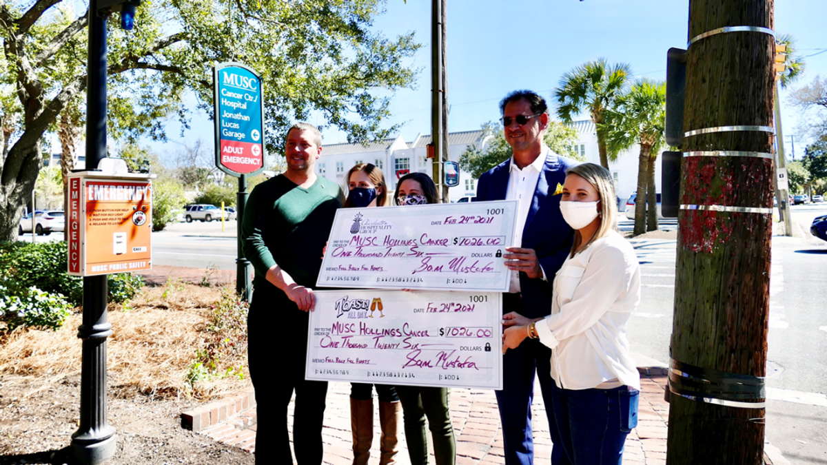 Charleston restaurateur, Sam Mustafa, presents two checks, totaling over $2,000 to the MUSC Hollings Cancer Center in honor of Breast Cancer Awareness month.